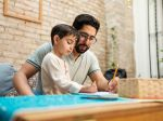 A young mexican father and his little boy sitting in front of the coffee table at home and drawing on a notebook with a pencil and a crayon.